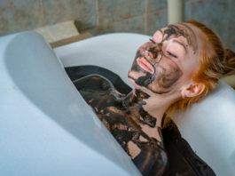 Ruda kobieta w kąpieli borowinowej