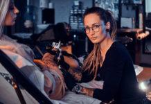 dziewczyna z dredami i tatuażami wykonująca tatuaż klientce na udzie