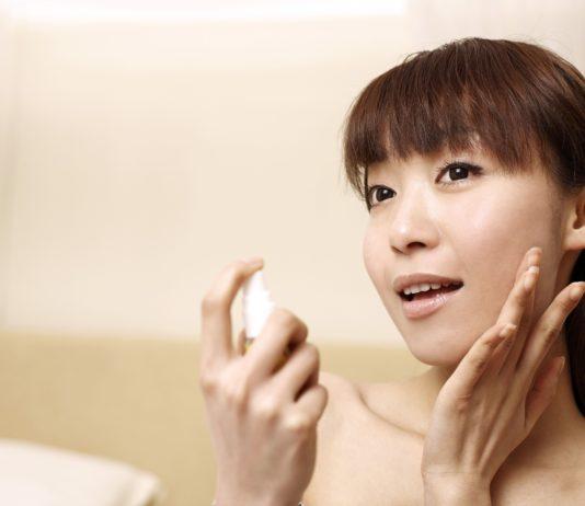 Koreanka wykonująca makijaż przed lustrem