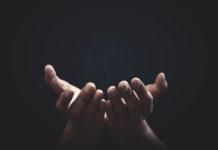 wyciągnięte kobiece dłonie na czarnym tle