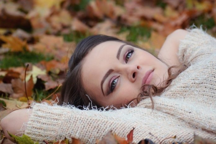 Kobieta leży na trawie i jesiennych liściach
