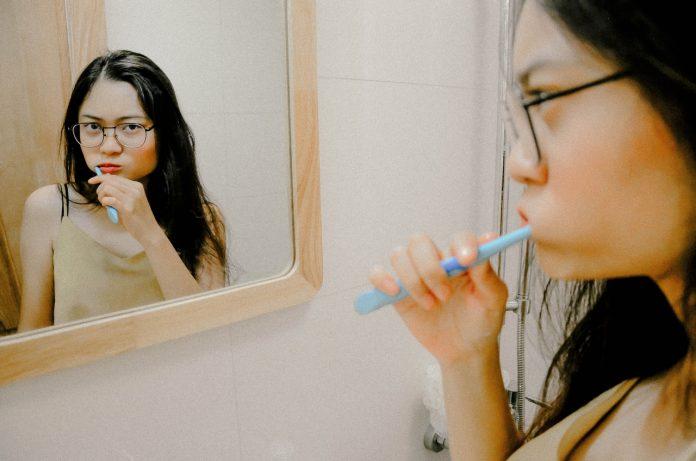 kobieta myjąca przed lustrem