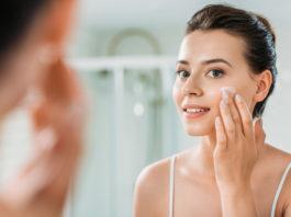 kobieta nakładająca krem na twarz przed lustrem
