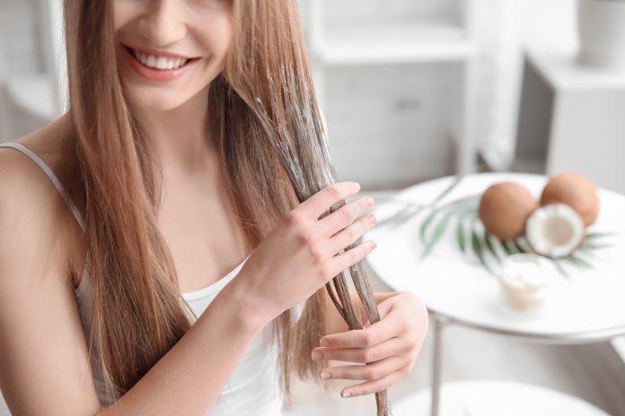 kobieta nakładająca odżywkę na włosy