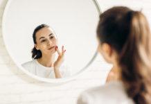 Kobieta w łązience przed lustrem robiąca makijaż