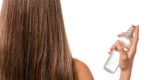 kobieta spryskująca włosy sprayem