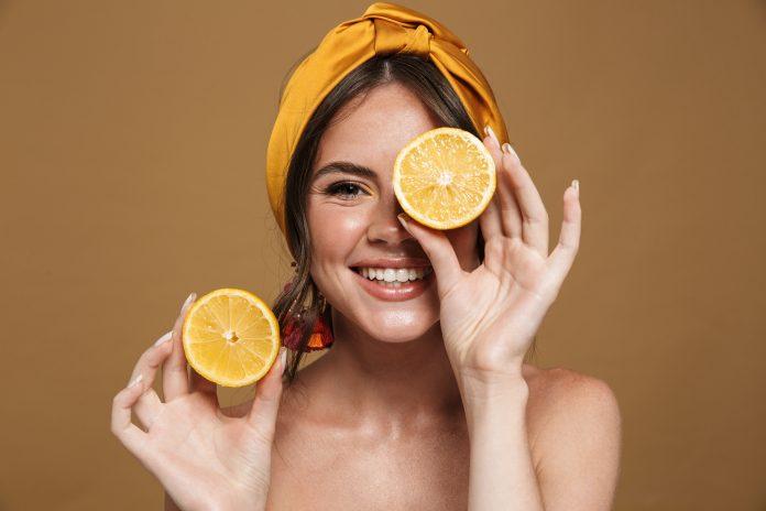 kobieta trzymająca cytryny przy twarzy