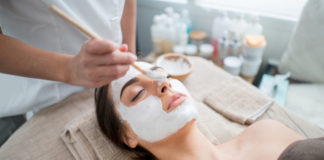 kobieta podczas zabiegu w gabinecie kosmetycznym z kremową maską na twarzy