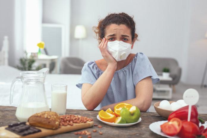 Young womanzmartwiona kobieta w masce przy stole z jedzeniem feeling upset about her multiple allergies