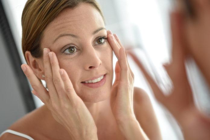 Kobieta w średnim wieku przegląda się w lustrze