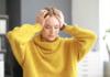 kobieta w żółtym swetrze ból głowy