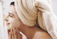 Kobieta z ręcznikiem na głowie nakładająca na twarz peeling