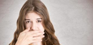 kobieta zasłaniająca ręką usta