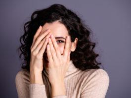 kobieta zasłaniająca twarz dłońmi