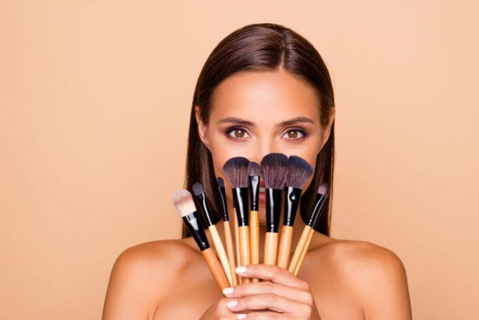 dziewczyna trzymająca w dłoniach pędzle do makijażu