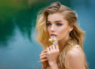 Piękna blondynka z kwiatem w dłoni na tle jeziora