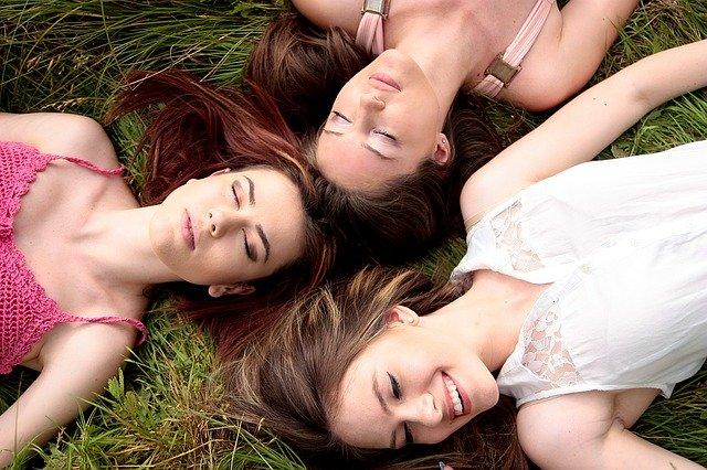 Trzy kobiety bez makijażu leżące na trawie