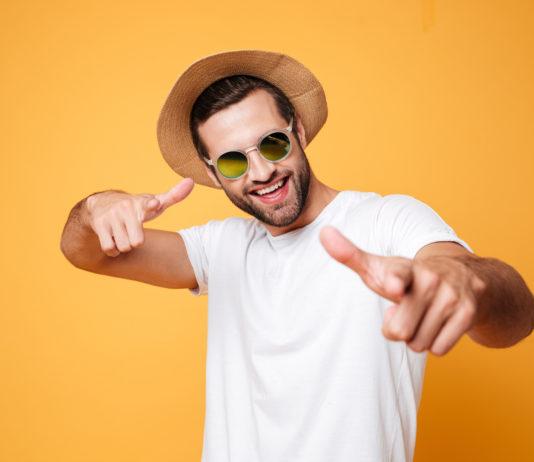 uśmiechnięty mężczyzna w letniej stylizacji na żółtym tle