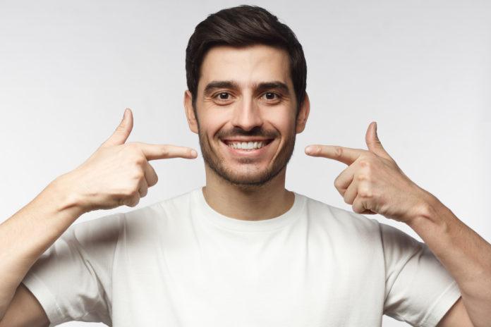 usmiechnięty mężczyzna wskazujący na swoje zęby