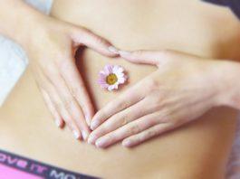 zbliżenie na kobiecy brzuch z kwiatkiem w pępku